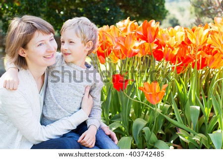 happy smiling mother and her loving son hugging and spending time together in the beautiful blooming park at spring time, mother's day concept - stock photo