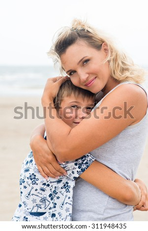Happy smiling mother and son having fun on the beach. - stock photo