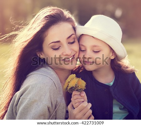 Happy smiling mother embracing her daughter in hat looking on yellow bright flowers on summer nature background. Closeup portrait of family love - stock photo
