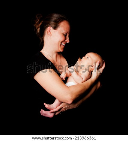Happy smiling mother holding baby infant in arms, on black. - stock photo