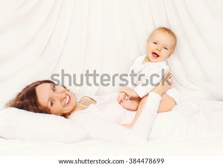 Happy smiling mother playing with baby lying on bed at home