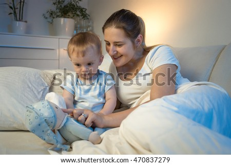 Happy smiling mother playing with her baby lying in bed at night and playing with toys