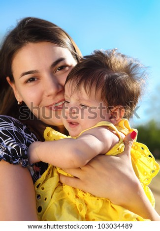Happy smiling mother with baby outdoors - stock photo