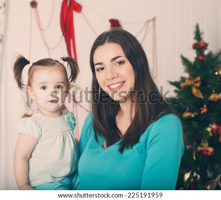 Happy smiling mother with daughter near the Christmas background