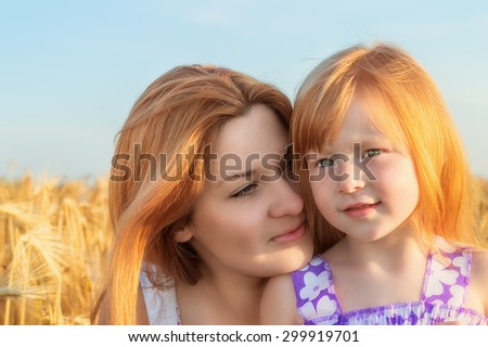 happy smiling mother with her little daughter gently hug in the background of a wheat field  - stock photo