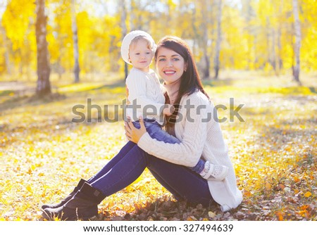 Happy smiling mother with little child playing in sunny autumn park - stock photo