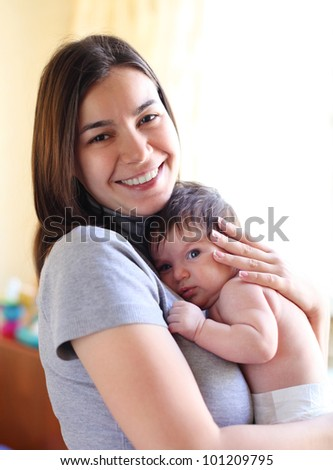 Happy smiling mother with one month old baby over white - stock photo