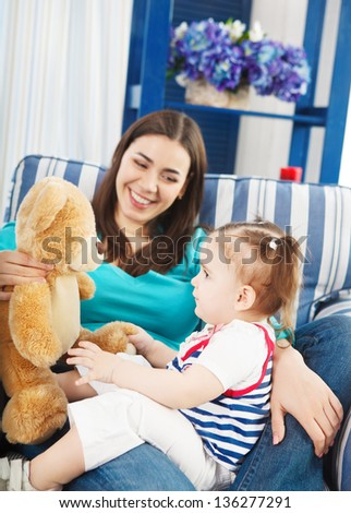 Happy smiling mother with one year old baby girl indoor - stock photo
