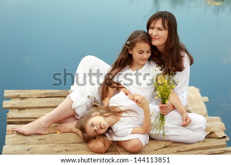 Happy smiling mother with two daughters sitting on the shore of the beautiful and clean lake in the countryside/Charming woman and two young children resting in the nature near the pond
