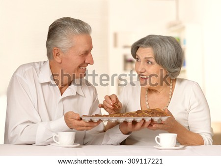 Happy smiling old couple with chocolate candies at home - stock photo