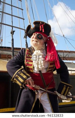 Happy smiling old pirate in colorful traditional costume stands on board ship and draws his sword. Schooner rigging and blue sky in background, vertical layout. - stock photo