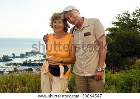 Happy smiling older couple outdoor by a lake - stock photo