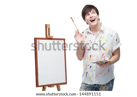 happy smiling painter standing near easel and holding palette and brush