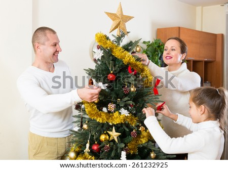 Happy smiling parents and girl decorating Christmas tree in the living room at home. Focus on man - stock photo