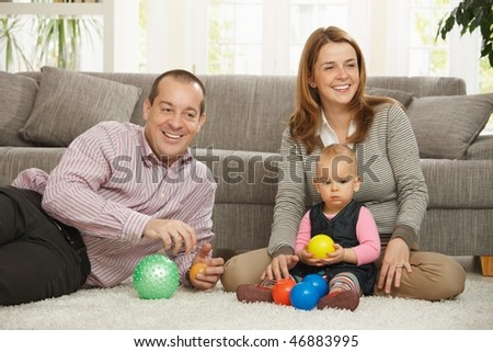 Happy smiling parents sitting with baby girl holding ball in hands at  home.
