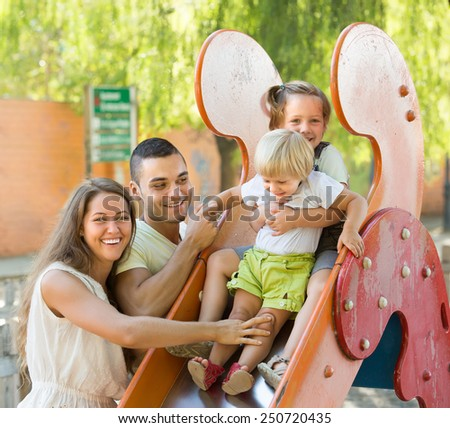 Happy smiling parents with two daughters playing at children's slide  - stock photo