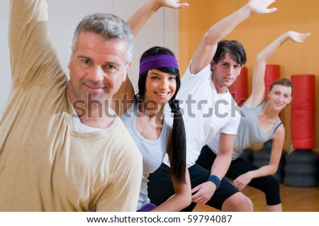 Happy smiling people doing aerobic exercises together at gym - stock photo