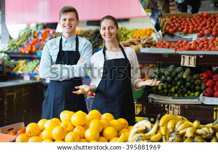 Happy smiling positive sellers having vegetables and fruits on displays of market