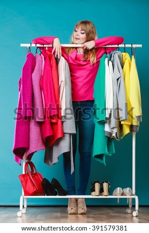 Happy smiling pretty woman choosing clothes to wear in wardrobe. Gorgeous young girl customer shopping in mall shop. Fashion clothing sale concept. - stock photo