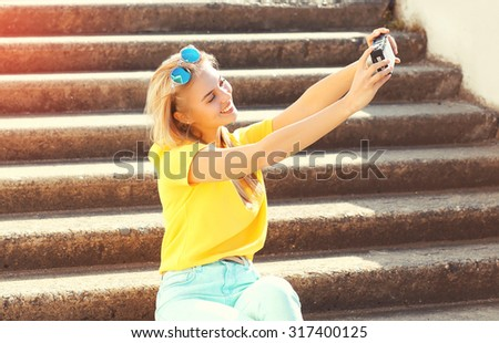 Happy smiling pretty young woman makes self-portrait on camera in the city - stock photo