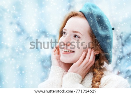 Happy smiling redhead girl with freckles touching her face, looking up. Model posing in street, wearing beret and sweater. Snowfall. Winter, Christmas holidays concept. Copy, empty space for text