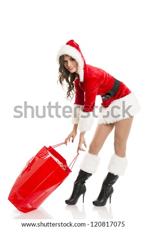 Happy smiling Santa girl dragging  heavy red shopping bag full of Christmas presents.
