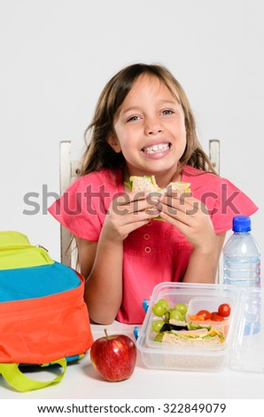 Happy smiling school girl eating her healthy lunch box sandwich with backpack and apple on the table - stock photo