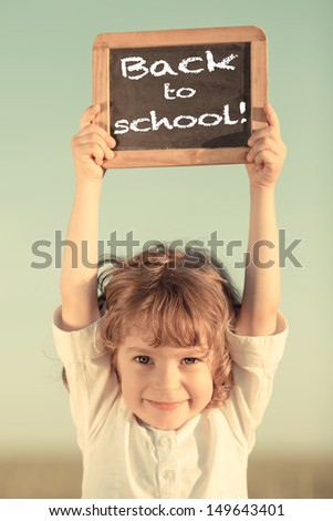 "Happy smiling schoolchild holding small blackboard with text ""back to school"" against sky background - stock photo"