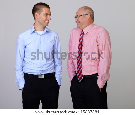 Happy smiling senior and junior businessman discuss something during their meeting with hands in pockets, isolated on grey - stock photo