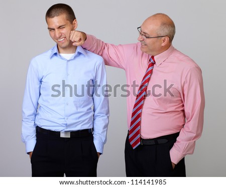 happy smiling senior businessman joke with junior businessman colleague, isolated on grey - stock photo