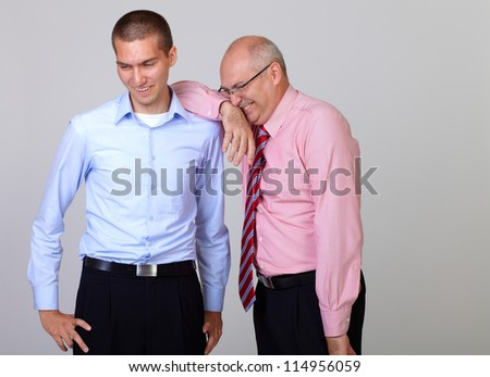 Happy smiling senior businessman leaning against his junior businessman colleague, isolated on grey - stock photo