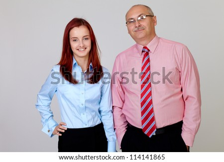 Happy smiling senior businessman with young attractive businesswoman in shirts, isolated on grey - stock photo