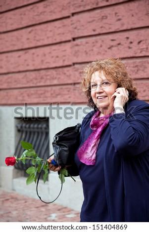 happy smiling senior lady on the phone, holding rose outdoors  - stock photo
