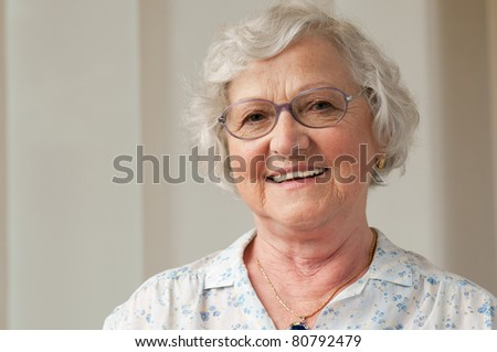 Happy smiling senior woman looking at camera at home - stock photo