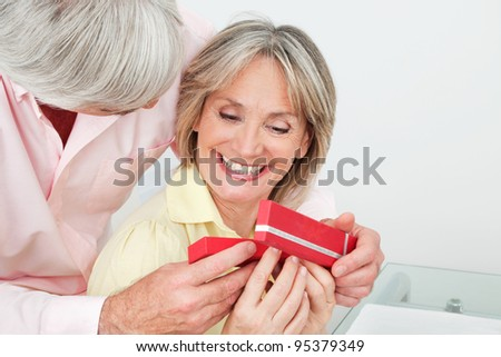 Happy smiling senior woman receiving gift from her husband - stock photo