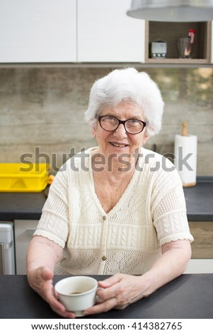 Happy smiling senior woman with cup of tea or coffee in the kitchen. - stock photo