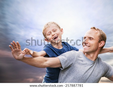 Happy smiling son and  father portrait over blue sky - stock photo