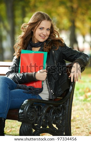 Happy smiling student girl sitting on bench at autumn outdoors with folders and worksheet copy-book