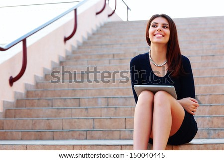 Happy smiling student sitting on stairs with a tablet computer - stock photo