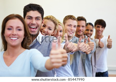 Happy smiling students in a row with their thumbs up - stock photo