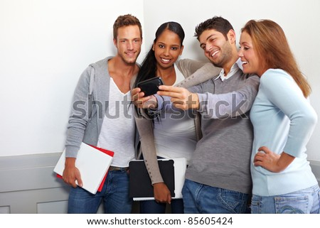 Happy smiling students taking group photos with smartphone - stock photo