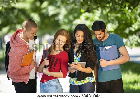 Happy smiling Students with tablet, computer at Park - stock photo