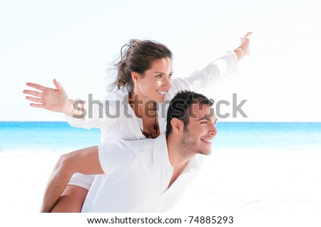 Happy smiling summer couple piggyback together with arms outstretched at beautiful beach