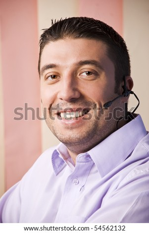 Happy smiling support operator man in lilla shirt on pink background - stock photo