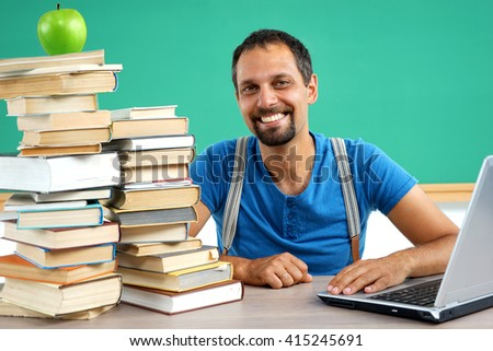 Happy smiling teacher at the classroom working with computer. Photo of smiling teacher, creative concept with Back to school theme - stock photo