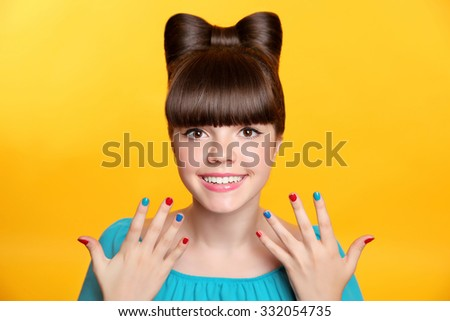 Happy smiling teen girl with bow hairstyle and colourful manicured polish nails. Funny girl showing ten fingers isolated on studio yellow background. - stock photo