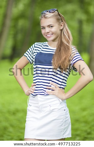 Happy Smiling Teenage Girl in Striped T-Shirt Posing Outdoors in Forest. Vertical Image Orientation