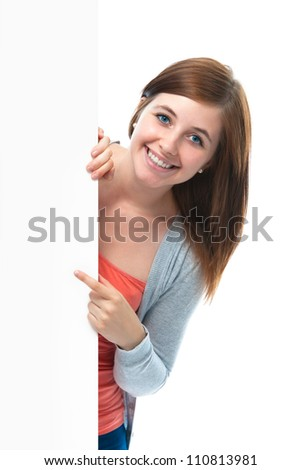 happy smiling teenage girl points her finger at a blank board - stock photo