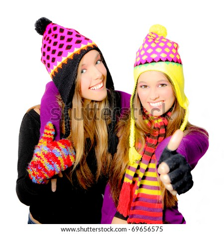 Happy smiling teenagers with winter hats showing thumbs up gesture - stock photo