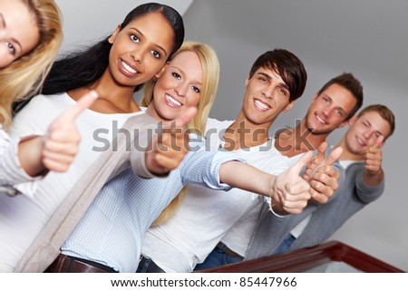 Happy smiling teens holding their thumbs up - stock photo